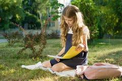 建立学校 小女孩有背包的一名小学学生坐秋天草读书学校笔记本 免版税库存图片