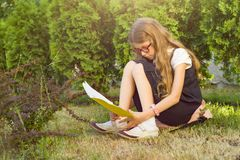 建立学校 小女孩有背包的一名小学学生坐秋天草读书学校笔记本 免版税库存照片