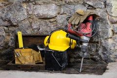 建筑为修建在一个石墙上的一个房子用工具加工 锤子、盔甲和其他必要的工具为建筑或分裂 免版税库存图片