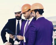 建筑和企业概念 有胡子的人和被集中的面孔谈论计划 建筑师的委员会佩带聪明 免版税库存照片