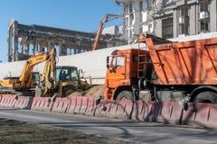建筑和路机械:一种挖掘机和一辆翻斗车在一工地工作大厦的爆破的 库存照片