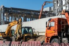 建筑和路机械:一种挖掘机和一辆翻斗车在一工地工作大厦的爆破的 免版税库存照片
