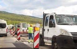建筑垄沟安装道路工程 在高速公路的整修 在建造场所的路机械 标志和信号 免版税库存照片