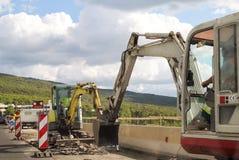 建筑垄沟安装道路工程 在高速公路的整修 在建造场所的路机械 标志和信号 图库摄影
