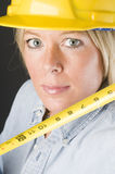 建筑女性安全帽盔甲俏丽的工作者 免版税库存照片