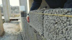 建筑工人修筑砖墙,在建造场所的特写镜头视图 股票录像