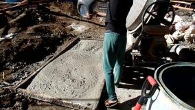 建筑工人倾吐在一台混凝土搅拌机的水在修建一个公立学校大厦 股票视频