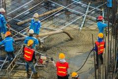 建筑工人倾吐在之后紧张地板工作的混凝土 运载从也混凝土泵或kn的泥工工作者水管 库存图片