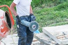 建筑工人切开有断电的一块石板材 库存图片