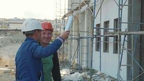 建筑工人和工程师谈话在建造场所站点 股票录像