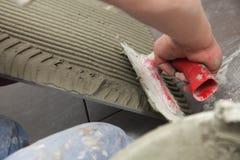 建筑工人在家铺磁砖砖地粘合剂 免版税库存照片