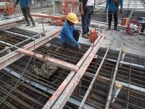 建筑工人在钢筋混凝土岗位紧张站点混凝土钢安装钢标尺 免版税库存照片