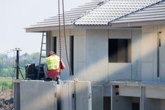 建筑工人安装起重机勾子在预制混凝土墙壁,预铸的房子 免版税库存照片
