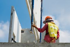 建筑工人安装预制混凝土墙壁、橙色安全帽和绿色背心 库存图片
