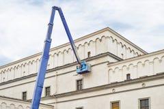 建筑工人定象使用举的景气机械的房子门面 免版税图库摄影