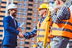 建筑工人播种的射击反射性背心的与商人握手 库存照片