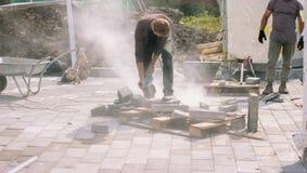 建筑工人用途电具体切削刀切开了一块石头 免版税库存照片