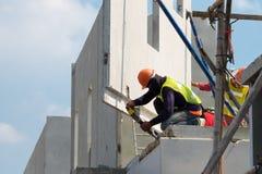 建筑工人用途电钻钻井混凝土墙在建筑区域,预铸的房子建筑 免版税库存照片