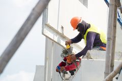 建筑工人用途电钻钻井混凝土墙在建筑区域,预铸的房子 库存图片