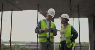建筑工人男人和建筑师妇女盔甲的,谈论房子的建筑计划,互相告诉 影视素材