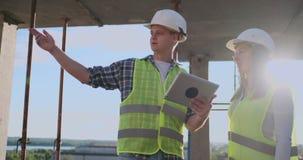 建筑工人男人和建筑师妇女盔甲的,谈论房子的建筑计划,互相告诉 股票视频