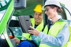 建筑工人谈论与工程师图纸 库存照片