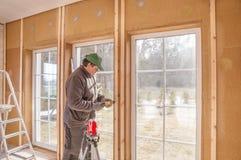 建筑工作,完成的工作在一个木房子和安装窗口使用激光的水平排行 免版税图库摄影