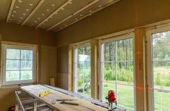 建筑工作,完成的工作在一个木房子和安装窗口使用激光的水平排行 库存照片
