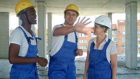 建筑工友谈论关于工作计划建造场所 库存照片