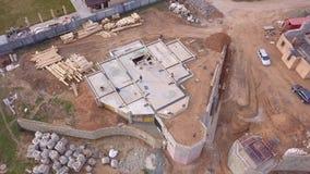 建筑工地和工作者鸟瞰图倾吐新房或车间的基础的混凝土在附近 影视素材