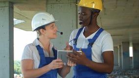 建筑工地的工程师使用数字式片剂和谈话 库存图片