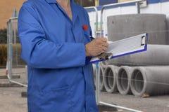 建筑工地的水管工检查数据表的 免版税库存照片