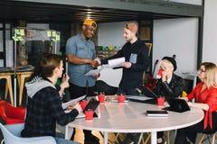 建筑师、坐在与膝上型计算机和片剂的表会议上的IT工作者或者设计师 两个创造性商人做 库存图片
