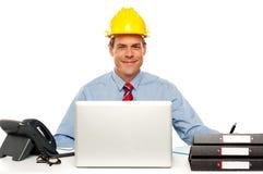 建筑师佩带的安全性帽子和使用膝上型计算机 免版税库存照片