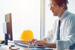 建筑师和工作在办公室的建筑工程师 免版税库存照片