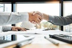 建筑师和工程师握手的建筑工人,当工作为配合和合作概念在的结束以后同意时 库存照片