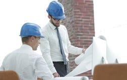 建筑师和谈论一个新的项目的建筑工头 库存照片