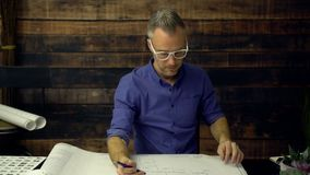 建筑师在书桌安置一个印刷品 股票录像