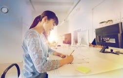建筑师在图纸的妇女图画在办公室 库存照片