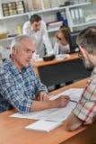 建筑师坐与过分要求的客户 免版税库存图片