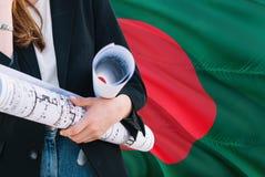 建筑师妇女反对孟加拉国挥动的旗子背景的藏品图纸 建筑和建筑学概念 免版税库存照片