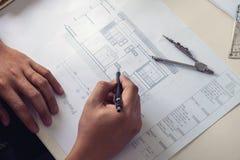 建筑师工作在图纸的,工程师与engineerin一起使用 图库摄影