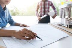 建筑师工作在图纸的,工程师与engineerin一起使用 免版税库存照片