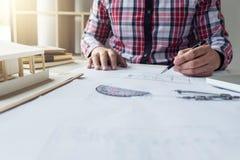 建筑师工作在图纸的,工程师与engineerin一起使用 免版税图库摄影