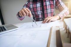 建筑师工作在图纸的,工程师与engineerin一起使用 库存图片