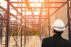 建筑师工程师检查工作建筑在一个建筑工地与日出光早晨 图库摄影