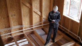 建筑师或建造者检查在一个半建造的木构架房子里计划 在一个建造场所的建造者有的文件 股票视频