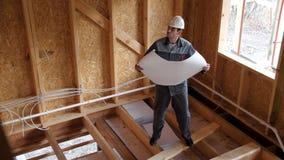 建筑师或建造者检查在一个半建造的木构架房子里计划 在一个建造场所的建造者有计划的 4K 股票视频