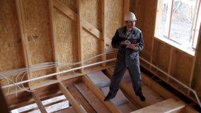 建筑师或建造者检查在一个半建造的木构架房子里计划 在一个建造场所的微笑的建造者有a的 影视素材