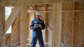 建筑师或建造者检查在一个半建造的木构架房子里计划 木的框架的建筑的工程师 影视素材